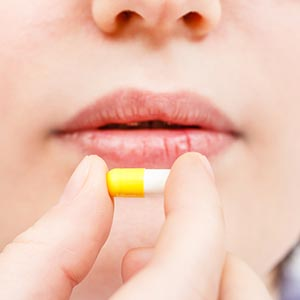 woman about to ingest an antibiotic