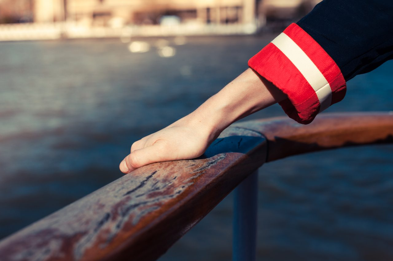 hand holding a railing on a ship