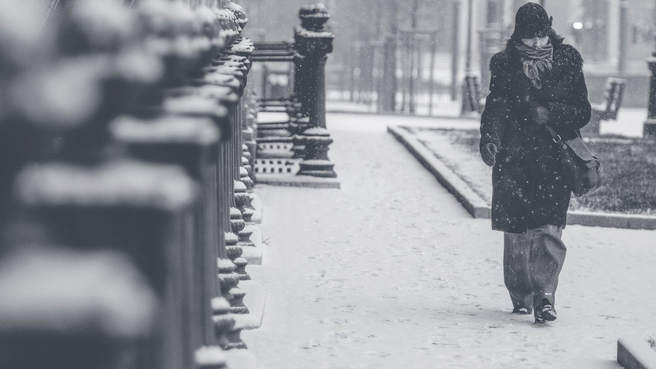 person wrapped up warm against the snow to stay well this winter