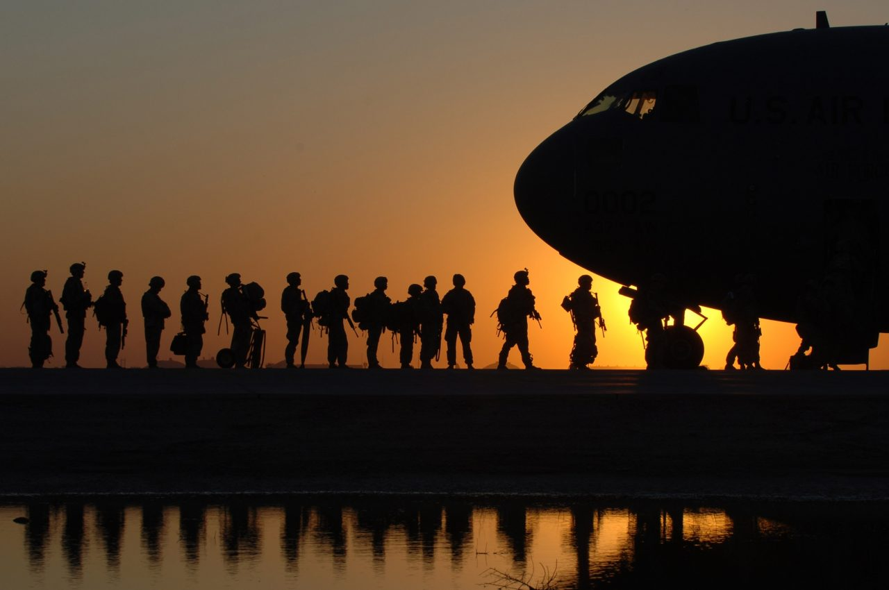 A queue of international travellers lining up for a plane, silhouetted against a yellow sunset.
